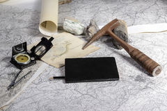 Geological expedition. The geological expedition is prepared with the study of topographic maps. On the table the tools of the geologist Royalty Free Stock Photo