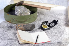 Geological expedition. The geological expedition is prepared with the study of topographic maps. On the table the tools of the geologist stock image