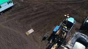 Geological exploration with new equipment aerial view. Wonderful aerial view small geological exploration station with powerful equipment among plowed field stock footage