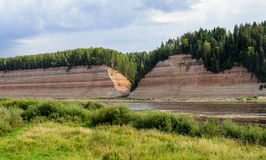 Geological outcrop on the riverbank with deep ravine Stock Photos