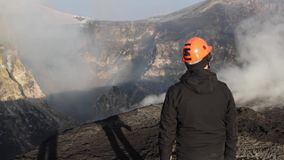 Geologist at the craters of the Etna volcano erupting stock video
