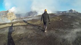 Geologist at the craters of the Etna volcano erupting stock footage