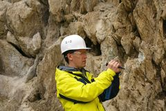 Geologist examines a sample of stone outdoor royalty free stock photo