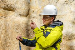 Geologist examines a sample of stone outdoor stock photography