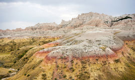 Geology Rock Formations Badlands National Park South Dakota. The clouds allow the sun to light rock formations in the South Dakota Badlands royalty free stock images