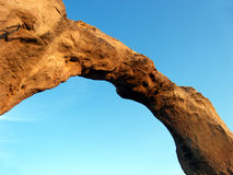 Geology's Creation. Red rock arch spanning a clear blue desert sky royalty free stock photography