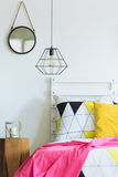 Geometric bedroom with round mirror Royalty Free Stock Photography