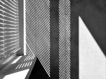 Geometric black and white composition. The plane of the plaster wall with a structural graphic shadow falling from the blinds. Horizontal view Stock Photos