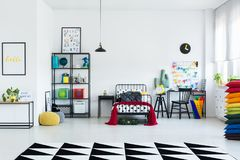 Geometric carpet in child`s room. Geometric carpet in spacious, bright child`s room with red blanket on bed and chair at desk royalty free stock photo