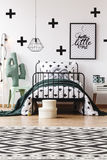 Geometric carpet in kids room. Black and white geometric carpet in kids room with toy on chair next to bed with grey pillow royalty free stock image
