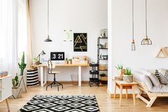Geometric carpet in multifunctional workspace. Black and white geometric carpet in multifunctional workspace with artwork on wall above desk royalty free stock photo