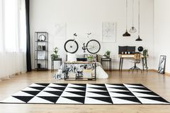 Geometric carpet in spacious bedroom. With bike on white wall above bed near desk with chair Stock Photo