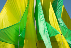 Geometric green yellow flags. Geometric holiday flags stretched on special ropes royalty free stock image