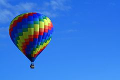Geometric Hot Air Balloon. A beautiful rainbow coloredf hot air balloon floats in a deep blue sky Stock Image