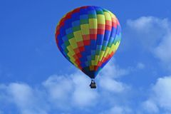 Geometric Hot Air Balloon. A beautiful rainbow coloredf hot air balloon floats in a deep blue sky Stock Photography
