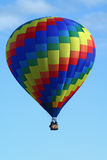 Geometric Hot Air Balloon. A beautiful rainbow coloredf hot air balloon floats in a blue sky Stock Photo