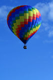 Geometric Hot Air Balloon. A beautiful rainbow coloredf hot air balloon floats in a blue sky Royalty Free Stock Images