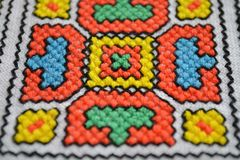 Geometric multi-colored pattern on white fabric embroidery top view royalty free stock photo