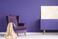 Geometric painting on a purple cabinet in elegant living room in. Terior with a blanket on a comfy armchair. Real photo royalty free stock image