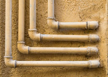Geometric pattern of 90 degree water pipes and fittings. Geometric pattern of four 90 degree water pipes and fittings on a plastered ocher wall Royalty Free Stock Image