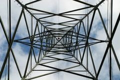 Geometric Pattern in an electricity pylon. The view from underneath an electricity pylon or transmission tower yields an intricate pattern of interconnected royalty free stock photography