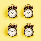 Geometric pattern of hands holding black alarm clock through hole in yellow paper background. Wake up alert concept. Morning. Routine. Minimalist style design royalty free stock photos