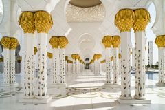 Columns and arabesques of Grand Mosque Abu Dhabi. Geometric pattern of pillars with decorated ceramic flowers and golden leaves in Sheikh Zayed Grand Mosque, Abu stock photos