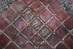 Geometric pattern of tin strips nailed to rusty metal sheet, painted in red and black sheets in top corners . Stock Photo