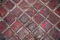 Geometric pattern of tin strips nailed to rusty and threadbare sheet metal, painted once in red. Royalty Free Stock Photos