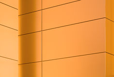 Geometric pattern on a wall of a modern building. Metal panels on a side of a modern building glowing in the sunset light - horizontal Royalty Free Stock Photography