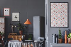 Geometric poster in dark room. Geometric poster on grey wall in dark dining room interior with orange lamp above table royalty free stock images