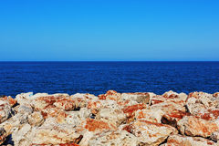 Geometric seascape with clear sky and rock line Royalty Free Stock Images