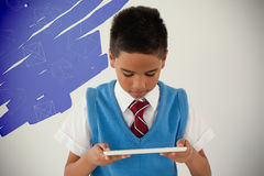 Composite image of geometric shapes on black scribbling. Geometric shapes on black scribbling against schoolboy using digital tablet Stock Photos