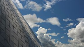 Geometric Sky. Interesting contrast of a beautiful blue sky full of clouds to the geometric buidling in the foreground Stock Photo