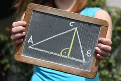 Geometric triangle. Sketched with chalk on slate shown by young female Royalty Free Stock Image