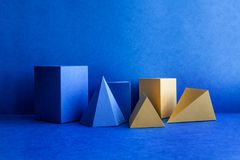Geometrical figures still life composition. Three-dimensional blue yellow prism pyramid tetrahedron rectangular cube. Objects on blue background. Platonic royalty free stock images