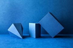 Geometrical figures still life composition. Three-dimensional prism pyramid tetrahedron rectangular cube objects on blue stock photos