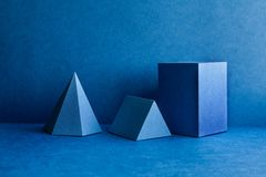 Geometrical figures still life composition. Three-dimensional prism pyramid tetrahedron rectangular cube objects on blue royalty free stock photography