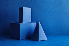 Geometrical figures still life composition. Three-dimensional prism pyramid tetrahedron rectangular cube objects on blue. Background. Platonic solids figures royalty free stock images