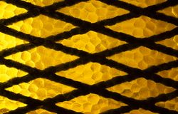 Geometrical Metal Grate and Yellow Decorative Glass royalty free stock images