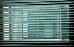 Geometrier på fönstret Persienner på kontorsfönstret att skapa en intressant lek av färger och färger, genom att dra ett raster fotografering för bildbyråer