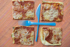 Geometries with pieces pizza and cutlery Royalty Free Stock Photos