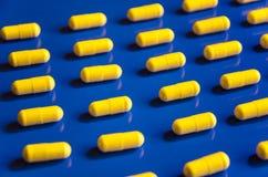 Geometrisch patroon van gele vitaminen in capsules op blauwe achtergrond stock fotografie