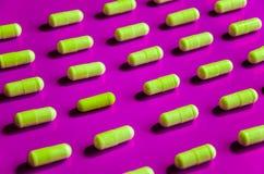Geometrisch patroon van gele vitaminen in capsules op roze achtergrond royalty-vrije stock foto's