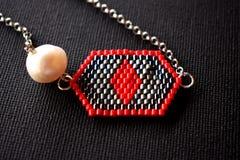 Geometrische geparelde halsband met parel op een zwarte oppervlakte Royalty-vrije Stock Fotografie