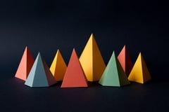 Geometrischer abstrakter Mehrfarbenhintergrund Helle Prismapyramiden-Dreieckform stellt auf dunklem Papier dar Violettes gelbes B Lizenzfreies Stockfoto