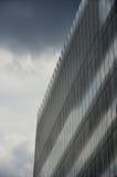 Geometrisches Bürohaus mit Wolke Stockbild