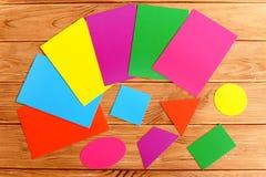 Geometriska former för färgrik papp Ark av kulör paperboard på en trätabell Royaltyfria Bilder