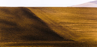 The geometry of Tuscan fields after harvest. Contrasting colors and textures with lines in shadow and light form the geometry of bare Tuscan fields royalty free stock photography