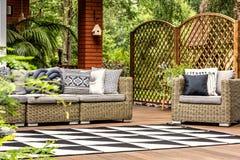 Geometryczny dywan na drewnianej werandzie z ogrodowym meble z pi fotografia royalty free